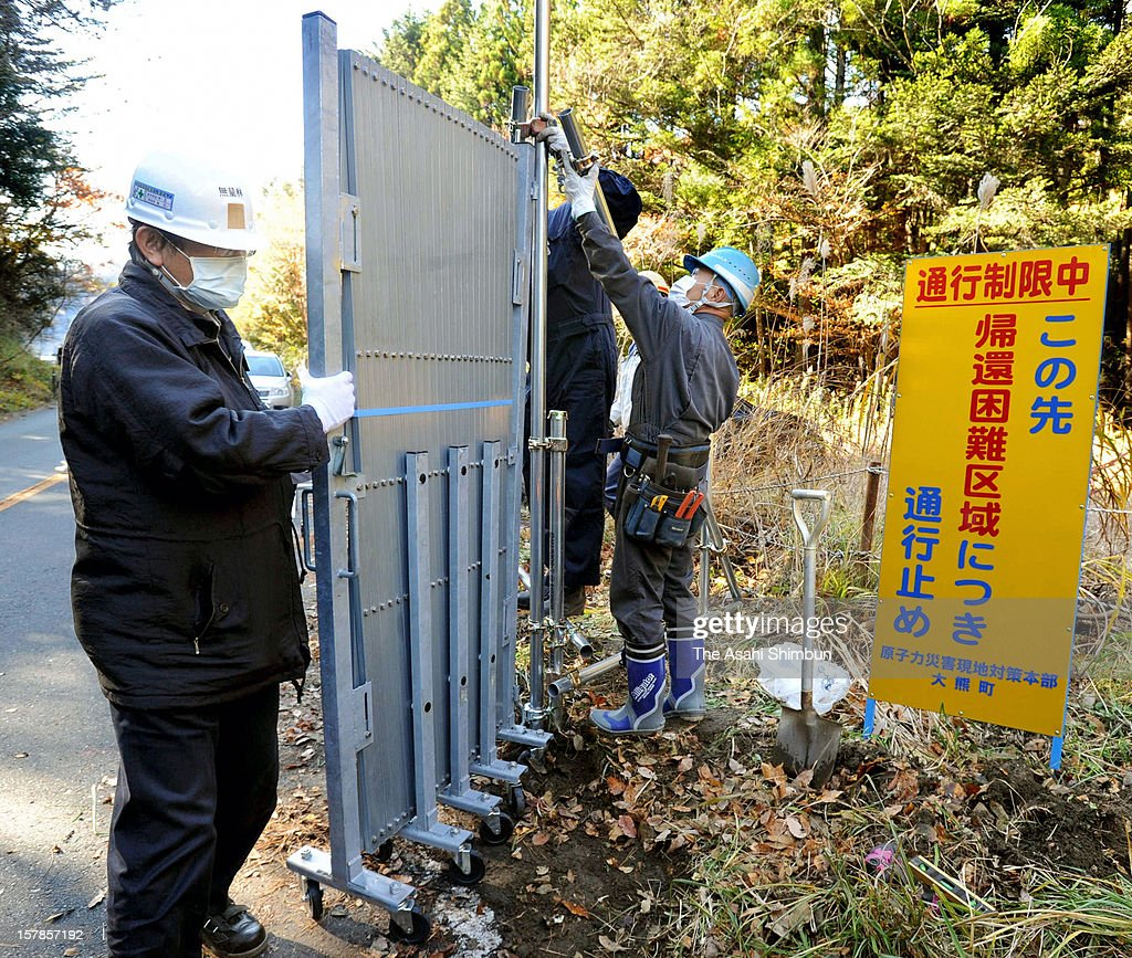 Workers set the gate to divide the area on December 7, 2012 in Okuma, Fukushima, Japan. Japanese government reclassified the area where 96 percent of Okuma city residents used to live as 'residents will face difficulties in returning for a long time' according to the radiation contamination level, will apply on December 10.