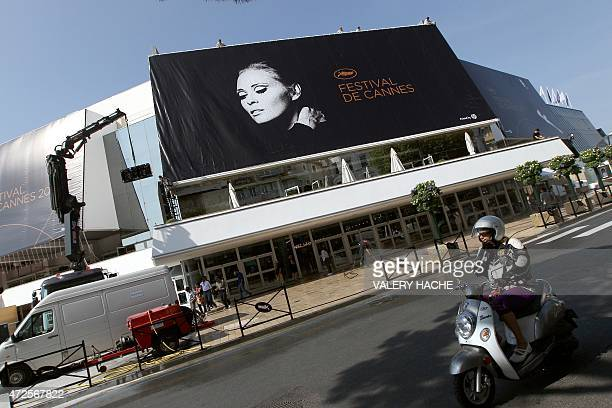 Workers set up a banner of the official poster of the 64th Cannes' film festival on May 9 2011 on the Festivals' palace facade in Cannes southeastern...