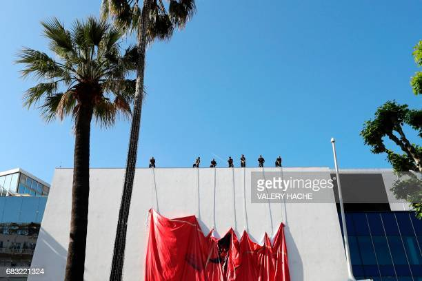 Workers set up a banner of the official poster of the 70th Cannes Film Festival on May 15 2017 on the facade of the Palais des Festivals in Cannes...