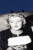 Workers set up a giant official poster of the 65th Cannes' film festival featuring late Marilyn Monroe on May 13 2012 on the facade of the Festivals'...