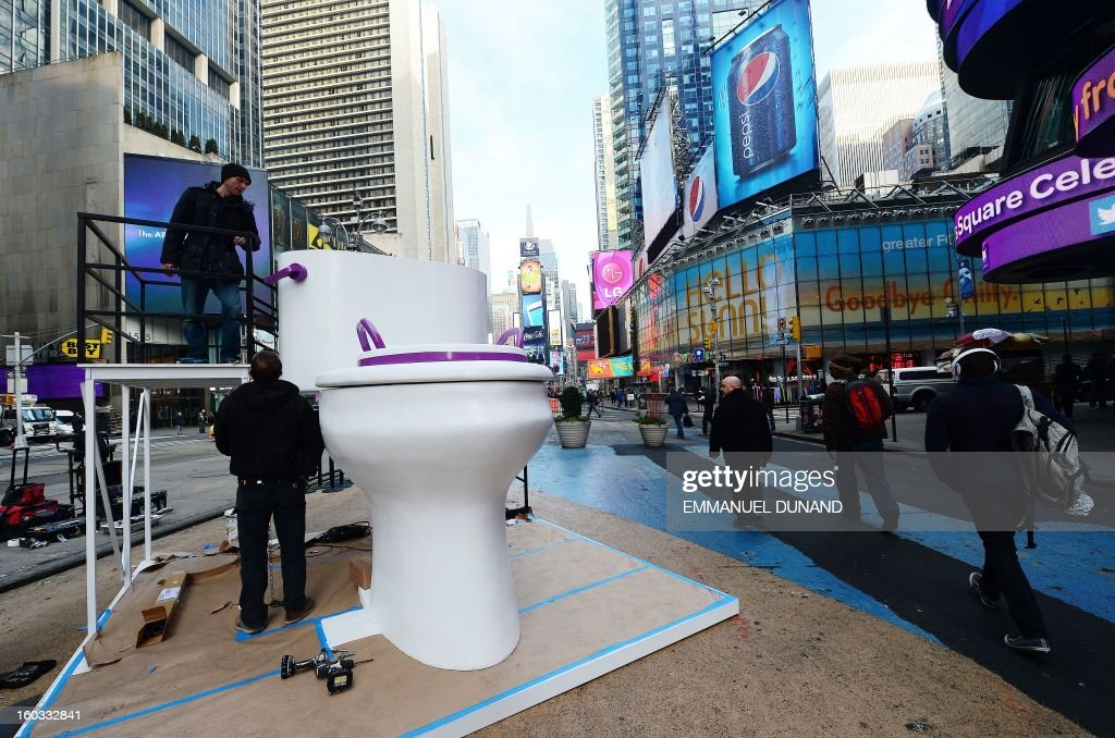 Workers set up a giant toilette as part of a promotional campaign for a diaper company on Times Square, in New York, January 29, 2013. AFP PHOTO/Emmanuel Dunand