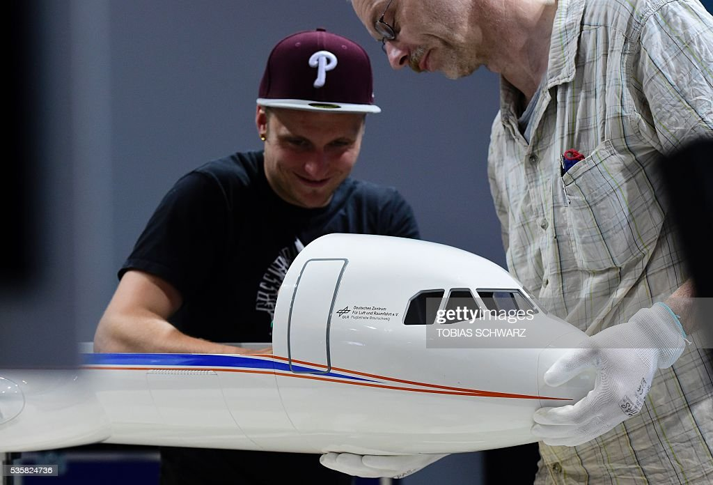 Workers set up a model of an 'ATRA' aircraft at the DLR booth at the International Aerospace Exhibition (ILA) in Schoenefeld on May 30, 2016. The Aerospace Exhibition at Schoenefeld Airport takes place from June 1 to 4, 2016. / AFP / TOBIAS