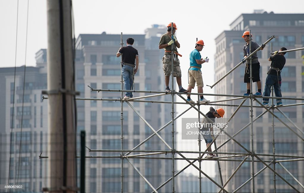 Workers set up a scaffolding on a building site in Shanghai on September 25, 2014. Concerns over China's economy -- a key driver of global growth -- have intensified following a string of lacklustre recent data, with economists calling for authorities to take further action to kickstart growth.