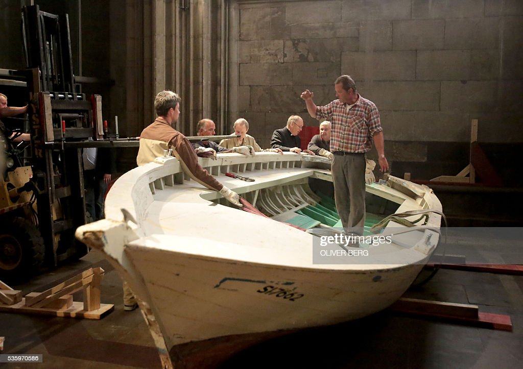 Workers set up a seven-meters long refugee boat in the Cologne Cathedral on May 31, 2016 in Cologne, western Germany. The boat, that served as altar during the 2016 Corpus Christi service held outside the Cathedral, will stay inside the church as a memorial during the 'Year of Mercy' proclaimed by Pope Francis. Several years ago, 80 to 100 people had managed to flee in the boat from Libya to Europe. / AFP / dpa / Oliver Berg / Germany OUT