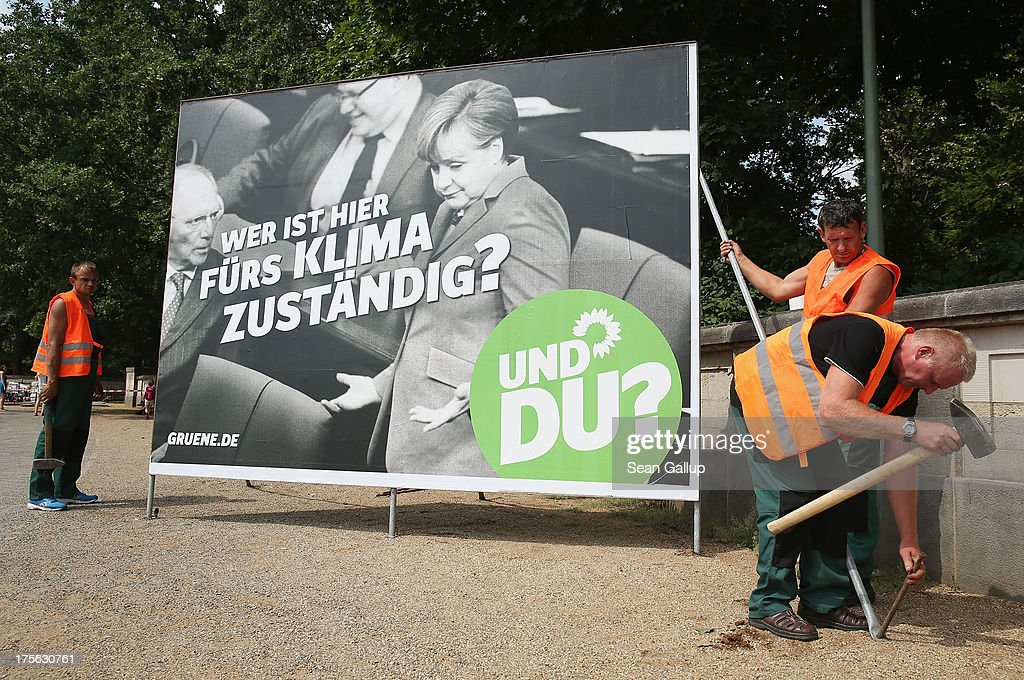 Workers set up an election campaign poster of the German Greens Party (Buendnis 90/Die Gruenen) that shows German Chancellor Angel Merkel and other members of her cabinet with a slogan that reads: 'Who's Responsible For The Climate Here? And you?' on August 6, 2013 in Berlin, Germany. Germany is scheduled to hold federal elections on September 22 and so far current Chancellor Angela Merkel and her party, the German Christian Democrats (CDU), have a strong lead over the opposition.