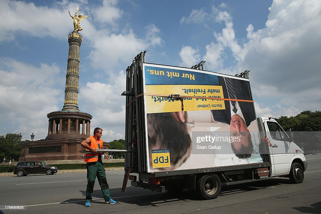 Workers set up election campaign posters, including one of the German Free democrats (FDP), in the city center on August 6, 2013 in Berlin, Germany. Germany is scheduled to hold federal elections on September 22 and so far current Chancellor Angela Merkel and her party, the German Christian Democrats (CDU), have a strong lead over the opposition.