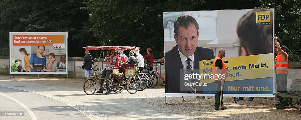 Workers set up election campaign posters of the German Christian Democrats (CDU), L, and German Free Democrats (FDP) in the city center on August 6, 2013 in Berlin, Germany. Germany is scheduled to hold federal elections on September 22 and so far current Chancellor Angela Merkel and her party, the German Christian Democrats (CDU), have a strong lead over the opposition.
