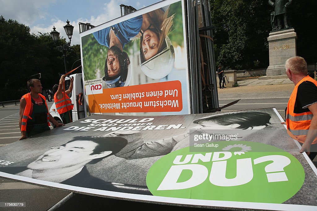 Workers set up election campaign posters of the German Greens Party (Buendnis 90/Die Gruenen) (below) and German Christian Democrats (CDU) on August 6, 2013 in Berlin, Germany. Germany is scheduled to hold federal elections on September 22 and so far current Chancellor Angela Merkel and her party, the German Christian Democrats (CDU), have a strong lead over the opposition.