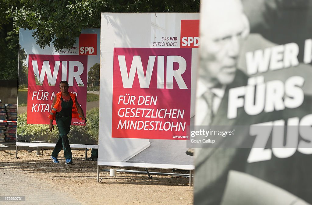 Workers set up election campaign posters of the German Social Democrats (SPD) and German Greens Party (R) on August 6, 2013 in Berlin, Germany. Germany is scheduled to hold federal elections on September 22 and so far current Chancellor Angela Merkel and her party, the German Christian Democrats (CDU), have a strong lead over the opposition.