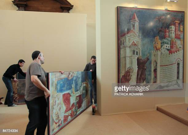 Workers set up Italian Giotto frescos by Italian photographer Antonio Quattrone on February 10 2009 at Paris' Notre Dame du Val de Grace church a...