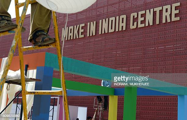 Workers set up stalls at the venue for the 'Make in India' showcase week in Mumbai on February 11 2016 Over 190 companies including national...