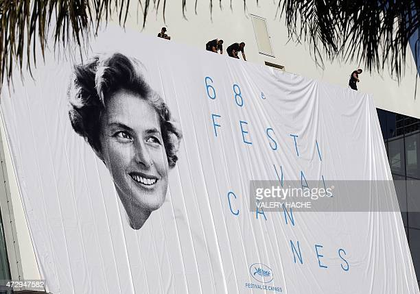 Workers set up the official poster of the 68th Cannes' film festival showing the Swedish actress Ingrid Bergman on May 11 2015 on the Festivals'...