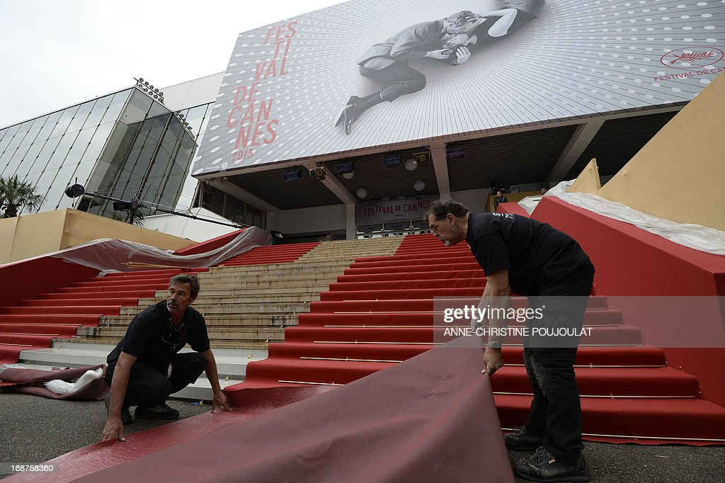 Workers set up the red carpet at the entrance of the Palais des Festivals on the opening day of the 66th edition of the Cannes Film Festival on May 15, 2013 in Cannes. Cannes, one of the world's top film festivals, opens today and will climax on May 26 with awards selected by a jury headed this year by Hollywood legend Steven Spielberg. AFP PHOTO / ANNE-CHRISTINE POUJOULAT