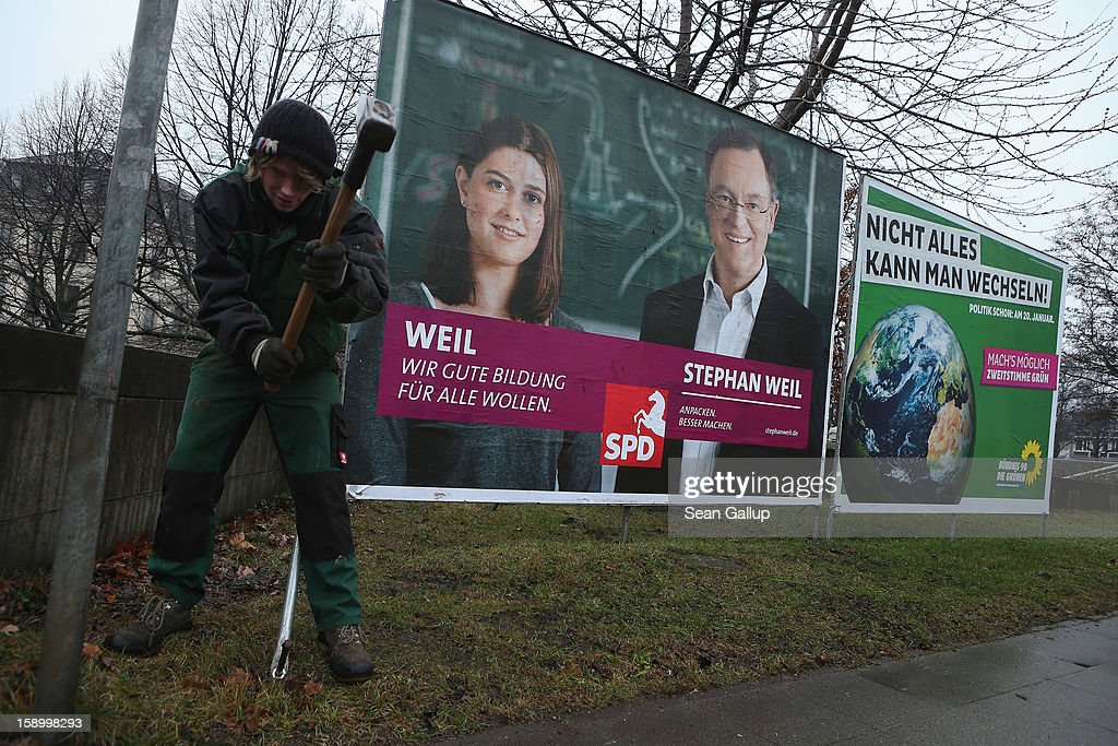 A workers sets up an election campaign billboard featuring Hanover Mayor and German Social Democrats (SPD) candidate Stephan Weil (L) next to one for the German Greens Party (Buendnis 90/Die Gruenen) on January 5, 2013 in Hanover, Germany. Lower Saxony is holding state elections on January 20 and many analysts see the election as a bellwether for national elections scheduled to take place later this year.