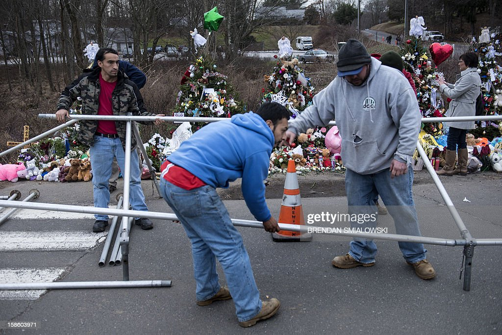 Workers setup a tent at a makeshift memorial near Sandy Hook Elementary School on December 20, 2012 in Newtown, Connecticut. People continue to mourn the killing of 20 students and 6 adults by alleged gunman Adam Lanza at Sandy Hook Elementary School last December 14. AFP PHOTO/Brendan SMIALOWSKI