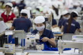 Workers sew clothing with sewing machines at the Esquel Group garment factory at the VietnamSingapore Industrial Park in Thuan An Binh Duong province...