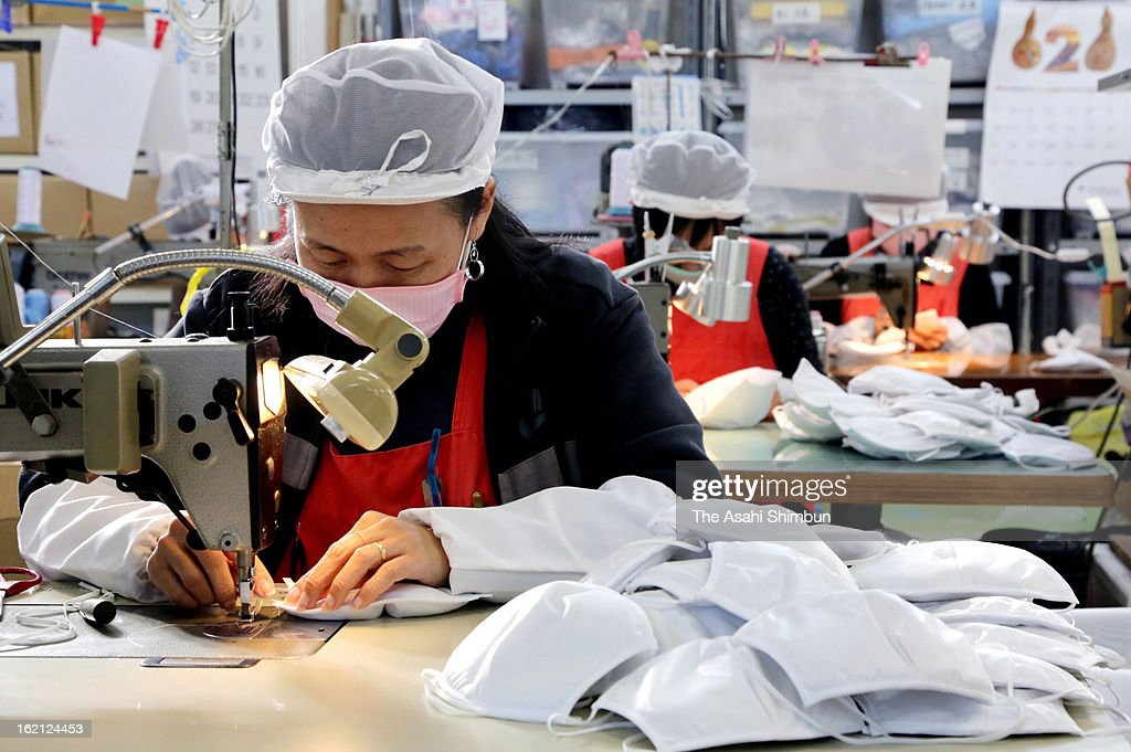 Workers sew ordermade masks, that shuts out particulate matter (PM) 2.5 as the mesh size of the mask is approximately 0.1 micrometers, at a mesh factory Clever on February 8, 2013 in Toyohashi, Aichi, Japan. The demand has been increasing since reports on China's pollution began, mainly from Japanese companies in China and Kyushu area.