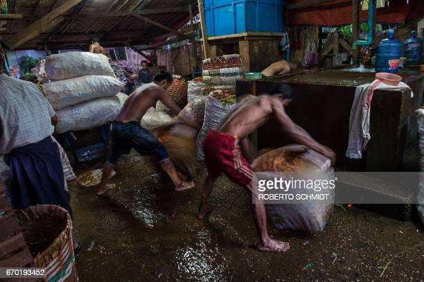 TOPSHOT Workers shake baskets filled with carrots drenched in water while cleaning them at a wholesale vegetable market in Yangon on April 19 2017 /...
