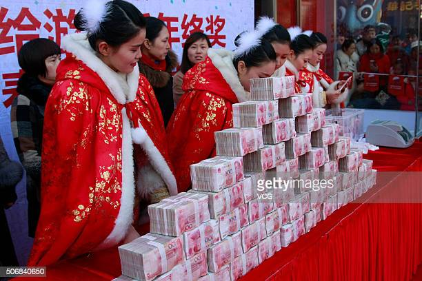 Workers show the 100yuan banknotes sent away by Song Dynasty Town as a feedback to the tourists on January 26 2016 in Hangzhou Zhejiang Province of...