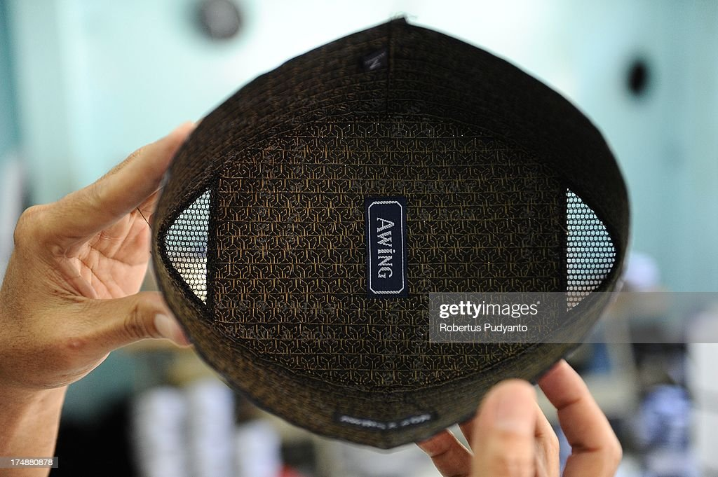 Workers show two ventilation of Awing traditional Muslim skull cap on July 29, 2013 in Gresik, Java, Indonesia. Awing traditional Muslim skull cap manufacturers have received increased demand for their products from Singapore, Malaysia, Brunei Darussalam, as well as domestic buyers, with sales increasing from from 30,000 to 50,000 pieces during the Ramadan period. This skull cap does not crease and has the advantages of good ventilation. The paperless skull cap body is made from high quality velvet material imported from Korea and the United States, with lining materials imported from Japan.