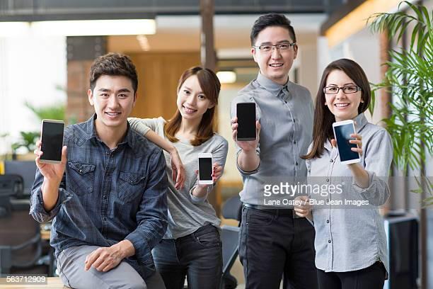 IT workers showing smart phones in office