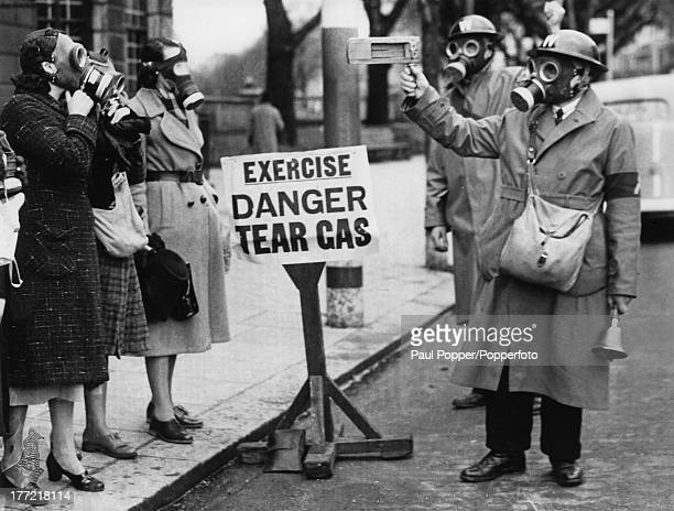 ARP workers signal with rattles to warn civilians to put on their gas masks during a gas attack drill using tear gas Brighton Sussex 7th February 1941