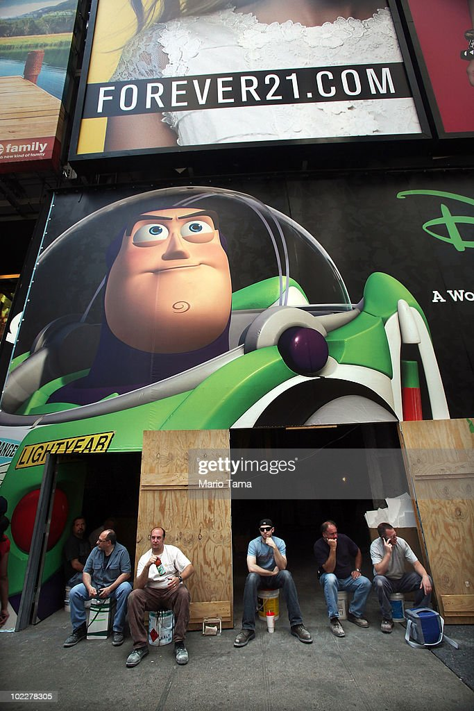Workers sit beneath a billboard for the movie Toy Story 3 in Times Square on June 21, 2010 in New York City. Accused Times Square bomber Faisal Shahzad is slated to be arraigned this afternoon on ten counts of terror and weapons charges.