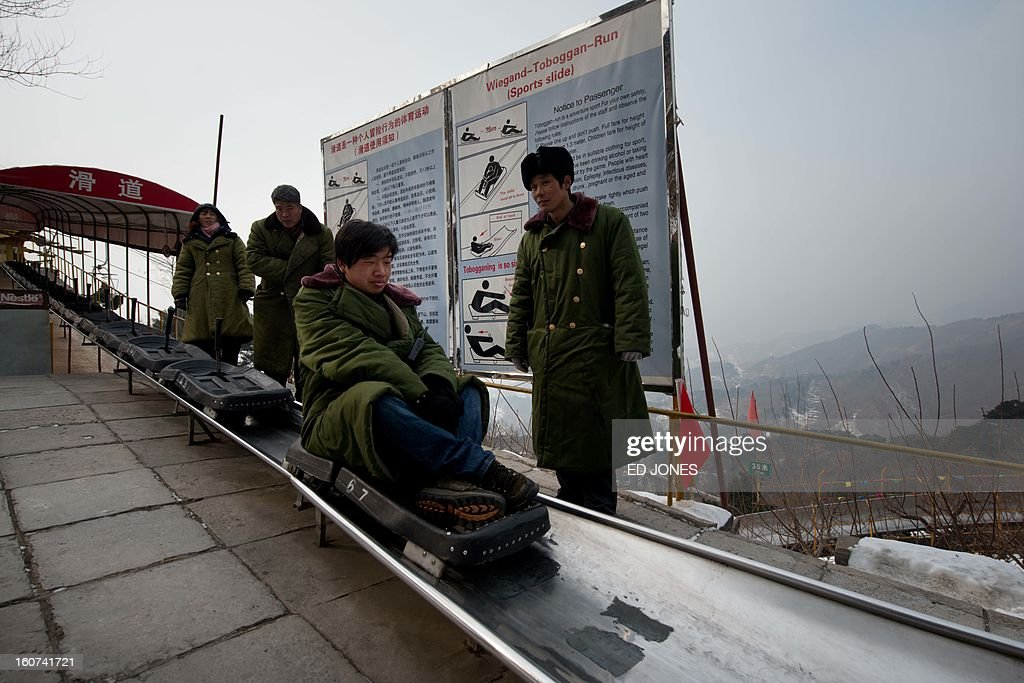 Workers sit on a tobogan on top of a hillside at the Great Wall of China in Mutianyu, near Beijing on February 5, 2012. China is preparing to welcome the lunar new year, or spring festival, which falls on February 10. AFP PHOTO / Ed Jones