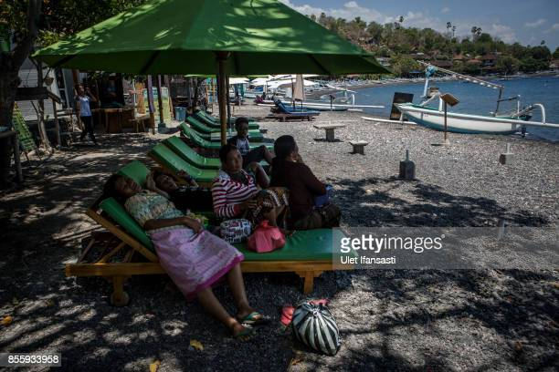 KARANGASEM BALI INDONESIA SEPTEMBER 30 Workers sit on sun lounger chair as emptied of tourists at Amed beach on September 30 2017 in Karangasem...