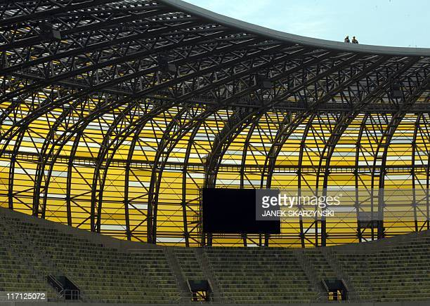 Workers sit on the roof of the PGE Arena football stadium in Gdansk northern Poland on June 22 2011 The stadium is one of the venues for the Euro...
