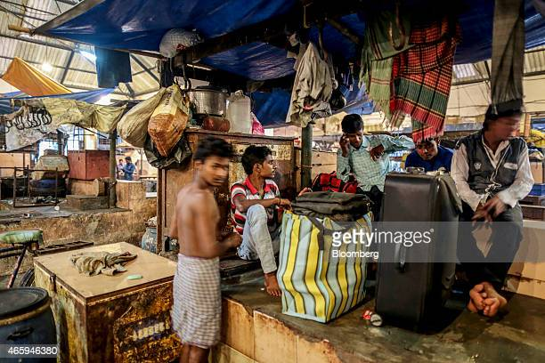 Workers sit with luggage at a closed beef stall inside Crawford Market in Mumbai India on Tuesday March 10 2015 The government of the state of...