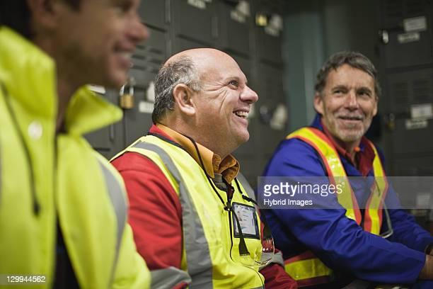 Workers sitting in locker room