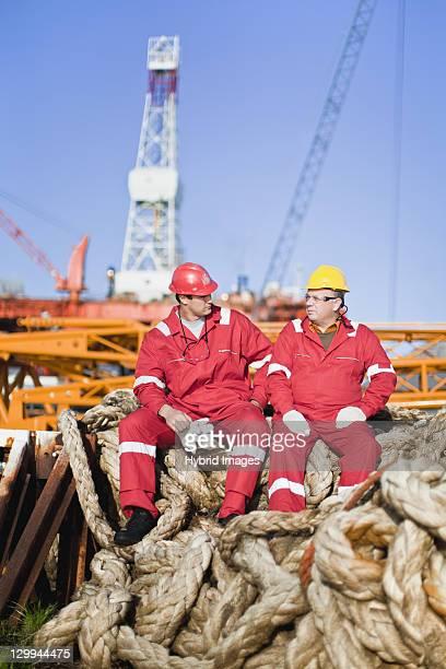 Lavoratori seduto sulla corda su oil rig