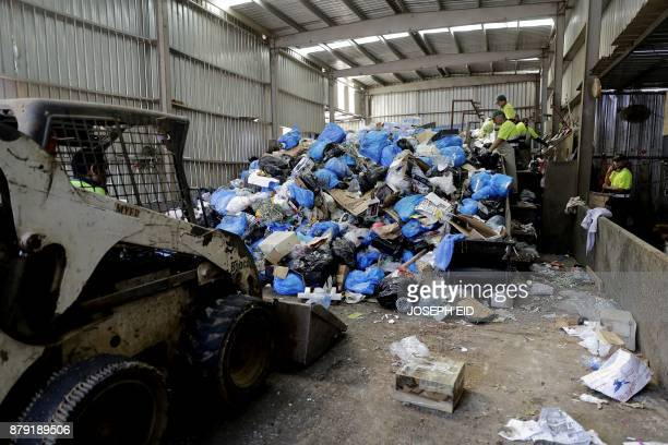Workers sort and separate garbage at a waste treatment plant in the area of Monteverde east of Beirut on October 27 2017 The Lebanese divers plunge...