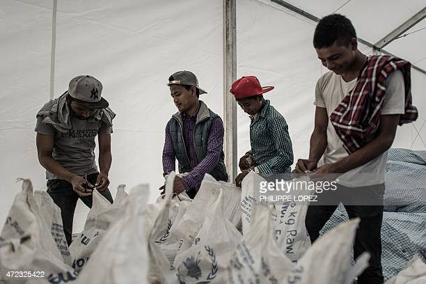 Workers sort bags of rice stored under a tent of the World Food Programme in Deurali village of Nepal's Gorkha district on May 6 2015 The earthquake...