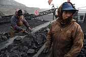 Workers sort coal on a conveyer belt near a coal mine in Datong in China's northern Shanxi province on November 20 2015 China will not improve on its...
