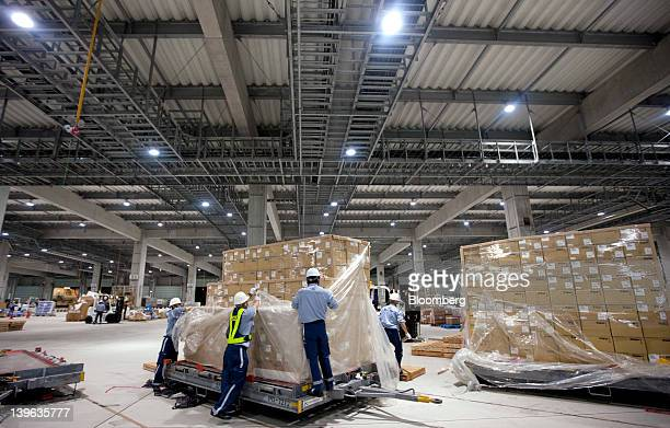 Workers sort packages at All Nippon Airways Co's cargo hub terminal at Naha Airport in Naha City Okinawa Prefecture Japan on Friday Feb 24 2012 ANA's...