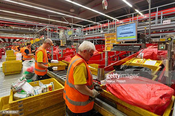 Workers sort parcels during the night at the DHL hub on February 27 2014 in Leipzig Germany The soon to be expanded hub handles 2000 tons of cargo or...