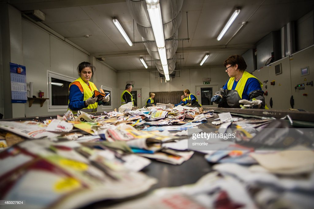 Workers sorting papers at recycling plant : Stock Photo