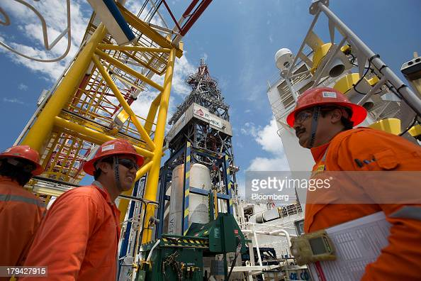 Workers speak while standing next to the drilling tower on the Petroleos Mexicanos La Muralla IV deep sea crude oil platform in the waters off...