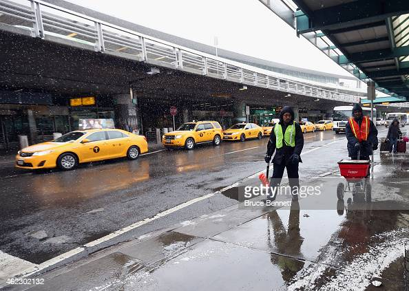 Workers spread salt just outside of the central terminal at Laguardia Airport on January 26 2015 in New York City Much of the Northeast is bracing...