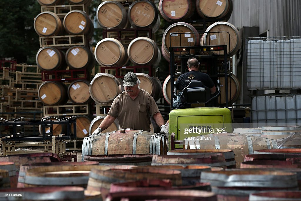 Workers stack broken wine barrels after a massive collapse at a wine barrel storage facility on August 25, 2014 in Napa, California. A day after a 6.0 earthquake rocked the Napa Valley, residents and wineries are continuing clean up operations.