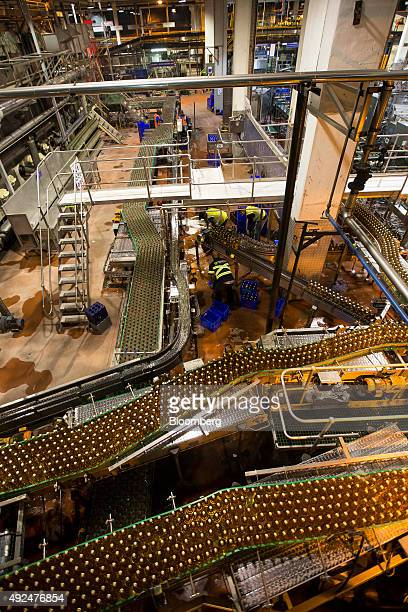 Workers stack crates as bottles of beer move along the production line at SABMiller Plc's Newlands brewery in Cape Town South Africa on Tuesday Oct...