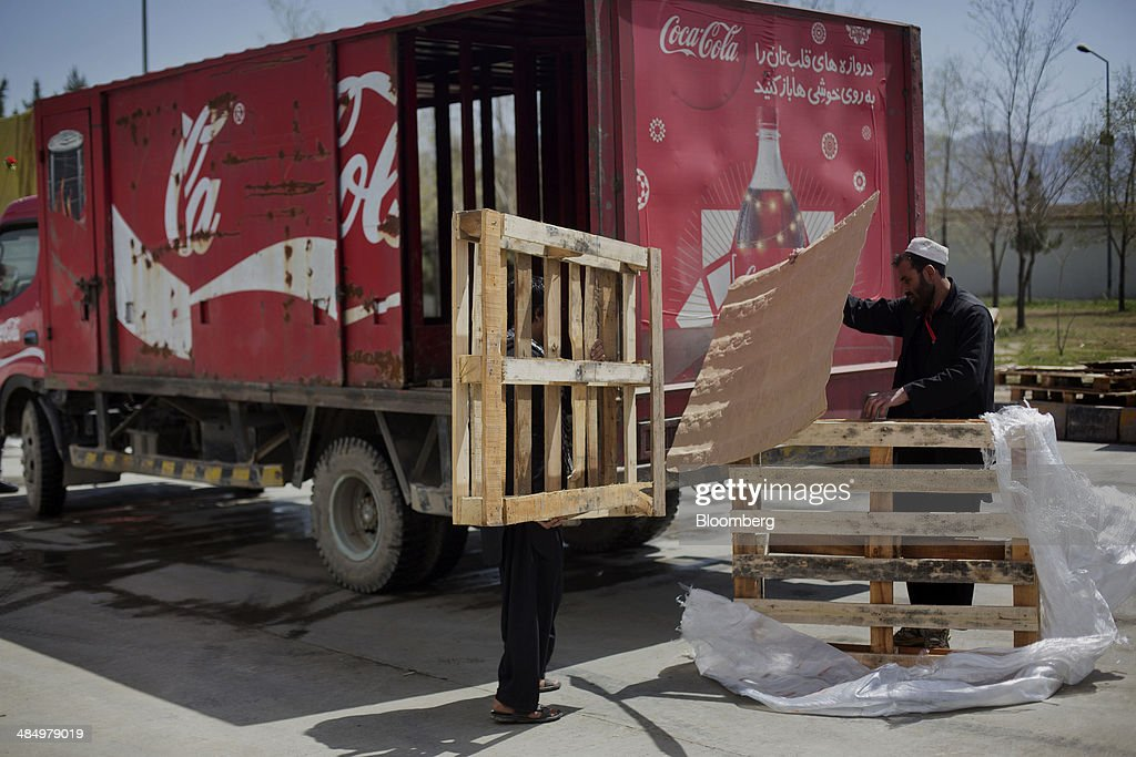 Workers stack pallets at the Habib Gulzar Non-Alcoholic Beverage Ltd. bottling facility in Kabul, Afghanistan, on Thursday, April 10, 2014. Coca-Cola Co., the world's largest soda maker, today showed signs of a rebound in the first three months of the year, easing the concerns that arose when the company unsettled investors with surprisingly sluggish global sales in the fourth quarter. Photographer: Victor J. Blue/Bloomberg via Getty Images