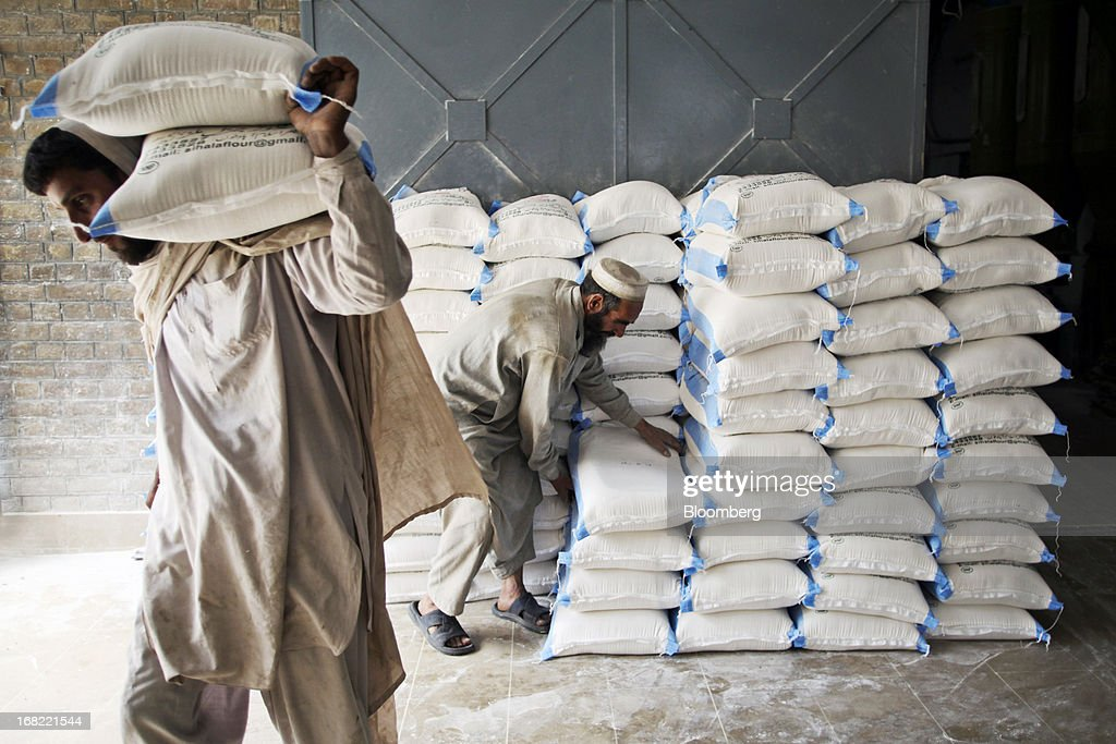 Workers stack sacks of wheat flour at the Sehila Flour Mill in Islamabad, Pakistan, on Saturday, May 4, 2013. Pakistan wheat output to increase this year, the U.S Department of Agriculture's Foreign Agricultural Service said in a report posted today on its website on April 4. Photographer: Asad Zaidi/Bloomberg via Getty Images
