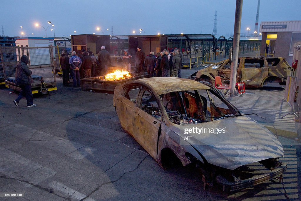 Workers stand arround a fire next to burnt cars at the assembly factory of Ford, on January 9, 2013 in Genk. A short majority of workers voted to start to work again, earlier this week, but some workers decided to block all access to the plant. Ford Europe announced end of October that the Ford Genk production plant will be closed by the end of 2014.