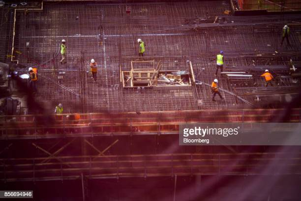 Workers stand at the 420 Kent Avenue apartment development under construction in the Williamsburg neighborhood of the Brooklyn borough of New York US...