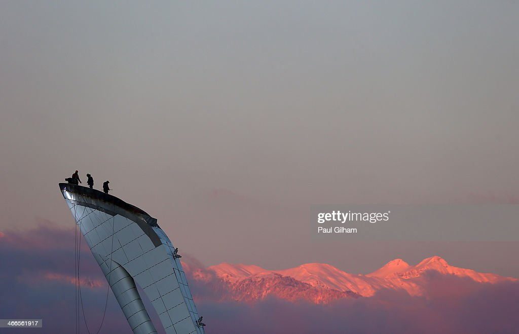 Workers stand atop the cauldron ahead of the Sochi 2014 Winter Olympics at Olympic Park on February 2, 2014 in Sochi, Russia.