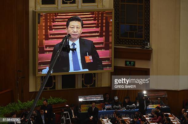 Workers stand below a live video image of Chinese President Xi Jinping during the opening session of the National People's Congress in the Great Hall...
