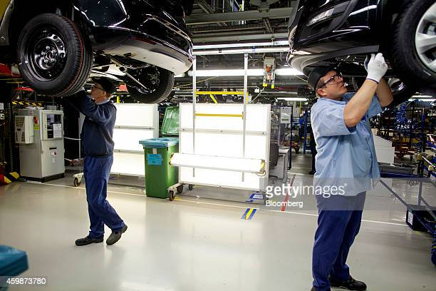 Workers stand beneath raised Opel Astra automobiles during assembly on the production line at General Motors Co's Adam Opel AG manufacturing plant in...